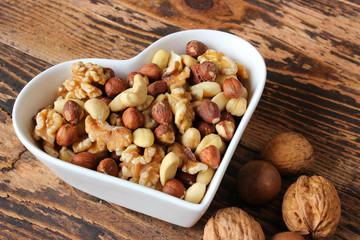 Verschiedene Nüsse in herzförmiger Schale
