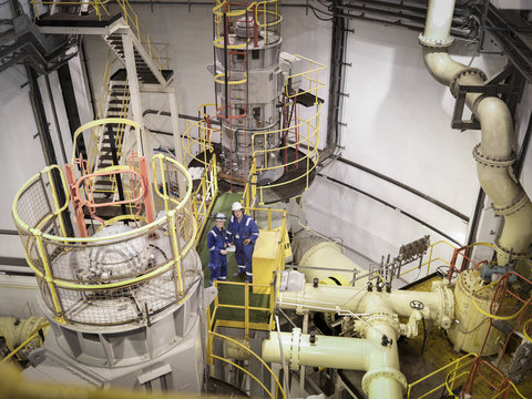Engineers in seawater pumping station of power station, high angle view