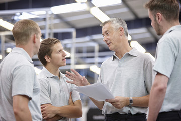 Manager and workers meeting in engineering factory
