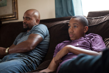 Father and son sitting on sofa watching tv