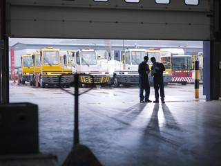 Engineers silhouetted in doorway in truck repair factory