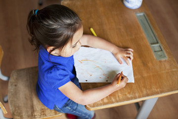 Girl drawing picture on desk, high angle
