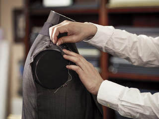 Tailor pinning garment in traditional tailors shop