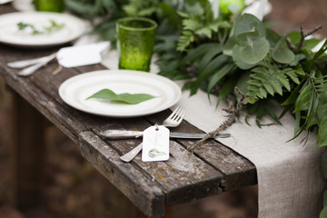 White plate with green leave and silver spoon and fork with blank label on wooden table and linen tablecloth