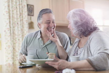 Affectionate mature adult couple sharing breakfast at home