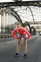 Young female runner preparing for run on bridge