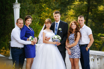 portrait of newlywed couple with bridesmaids and groomsmen in green sunny park