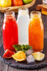 Fresh citrus juices on a dark wooden background.