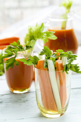 Fresh carrots and celery in glass with fresh carrot juice and parsley on black background