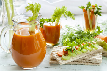 Plain rye cakes, galette rye with fresh carrots, celery and parsley around fresh carrot juice, fresh carrot and celery on light background