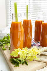 Natural and fresh carrot juice in small bottles with fresh celery and plain rye cakes, galette rye on light background