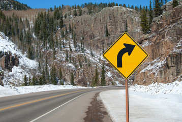 Right Curve Sign:  A sign warns of a right turn ahead on a mountain road in southern Colorado.