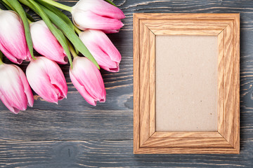 Fresh pink tulips and blank frame