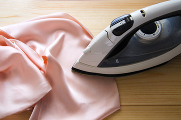 Electric iron on pink silk fabric