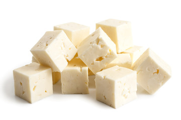 Square cubes of feta cheese isolated on white.