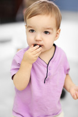 Portrait of cute cheerful boy eating candy