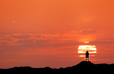 Sunset landscape with silhouette of a standing happy man against the sun and colorful sky on the mountain in summer. Travel background