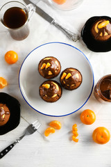 Three tasty cupcakes with slice of mandarin and chocolate on a plate over light wooden background