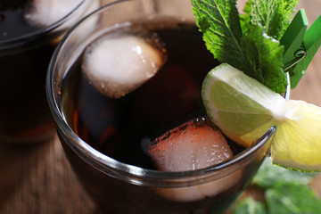 Glass of cola with ice, mint and lime on wooden table background, closeup