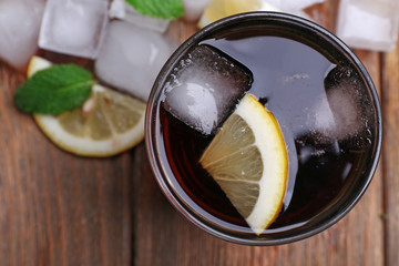 Glass of cola with cubes of ice and lemon , closeup