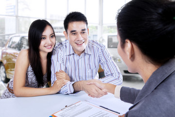 Car buyer shaking hands with car dealer