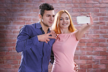 Young attractive couple taking selfie with mobile phone on brick wall background