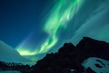 Wall Mural - Northern Lights over volcanic rock formations in Iceland
