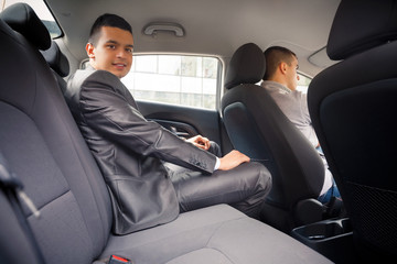 Young businessman is looking at camera while sitting on back seat of the car, while his chauffeur is driving automobile.
