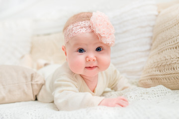 Smiling baby girl with chubby cheeks and big blue eyes wearing white clothes and pink band with flower lying on bed and looking at camera. Babyhood and childhood concept