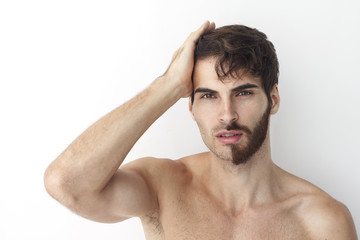 Man without a shirt, standing in front of a camera on a white background with half of his face with scruffy beard and messy hair, the other half has trimmed beards.