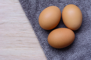 Fresh eggs on wooden and Microfiber Cloth background