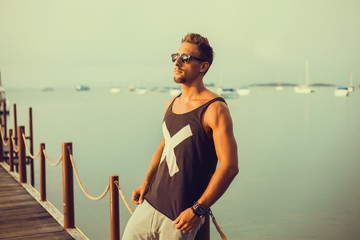 young guy with a beard in a t-shirt and sunglasses posing on the pier,Rugged and manly. Confident young bearded man looking at camera and adjusting eyewear while standing outdoors