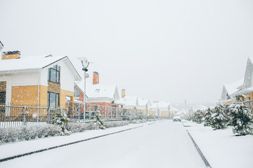 Row of the snowbound houses, homes with the sidewalk on empty street