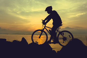 Healthy lifestyle. Silhouette of bicyclist riding the bike at seaside.
