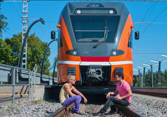 Young trendy guys in front of train