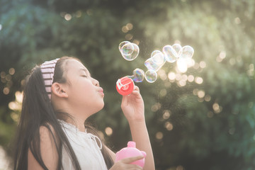 Cute asian girl is blowing a soap bubble