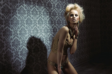 Sensual blond lady posing in a mysterious room