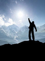 Winner silhouette on the mountain top. Sport and active life concept.