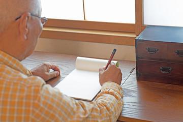 シニアが和室で手紙を書く