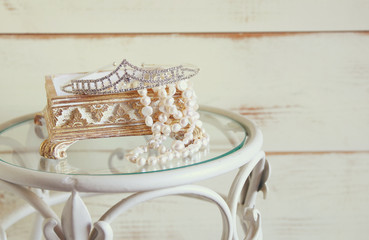 image of white pearls necklace and diamond tiara on vintage table. vintage filtered. selective focus