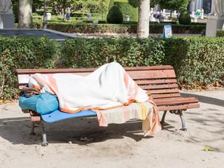 homeless man sleeping on a bench