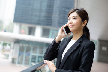Businesswoman talk to mobile phone in Hong Kong city