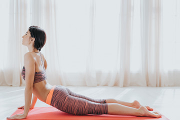 Beautiful fitness woman on a yoga mat in a white bright room, spring sunny day