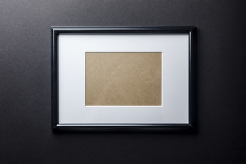 Black thin plain empty wood picture frame with white mat passe-partout on black wall background