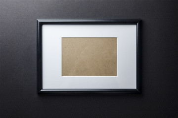 Black plain empty thin wood picture frame with white mat passe-partout on black bricks background