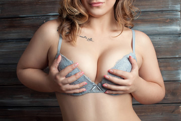 sexy girl in bra holds hands a breast