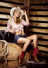 Sexy young blond cowgirl with fit body smiling on farm