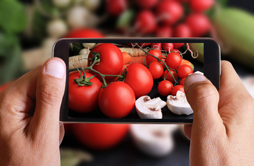 Male hand taking photo of Fresh, raw, organic vegetables on black background with cell, mobile phone. Cooking, Healthy eating concept.