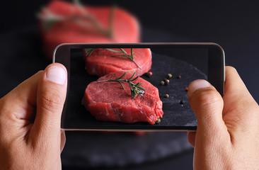 Male hand taking photo of raw beefsteak with spices and cherry tomatoes on wooden background with cell, mobile phone.