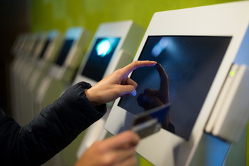 Woman using the self services terminal to pay on the fare